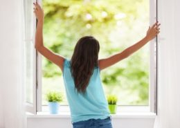 woman standing at open window
