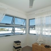 Grey framed awning windows in a room with sheer curtains