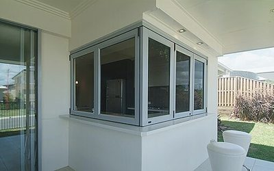 Bi fold windows installed on the corner of a white house