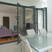 Bi-fold doors in a dining area opening into living room