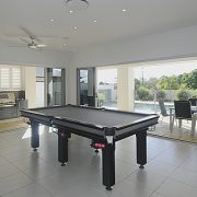 Snooker table in entertainment room with stacker doors opening into pool area