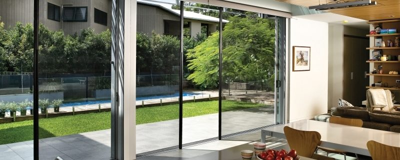 Bi fold screen double doors opening into lawn and pool area