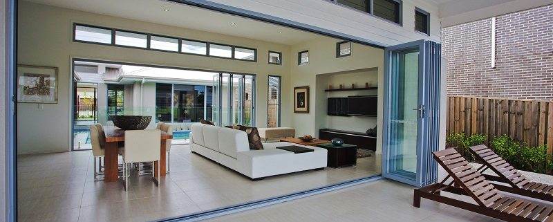Open bi-fold doors opening into large living room with dining area