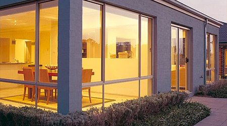 Outside view of a house with aluminium windows & sliding doors looking into dining area