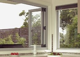 Open white frame aluminium bi-fold windows in a kitchen