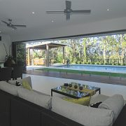 bi fold doors in a living room opening to a large pool area