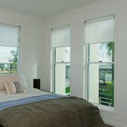 Bedroom with small bed & double hung windows