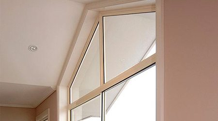 Angular fixed lite window in a peach color wall