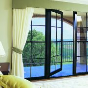 Black framed hinged door in a bed room opening to a balcony