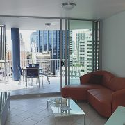 Sliding doors in a living room opening to balcony overlooking the city